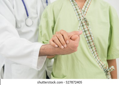 Caring doctor holding lady's hand with care.