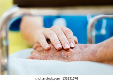 Caring doctor or nurse holding elderly lady's hands in wheelchair.