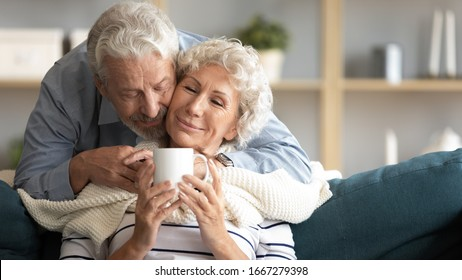 Caring elderly 60s husband caress hug middle-aged wife bring tea cover with blanket at home, happy old mature couple relax enjoy weekend in living room together show love and affection