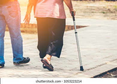 caring for the elderly concept. Professional assistant supporting elderly woman walking exercise together in park. carer supporting senior disabled woman with walking stick.
