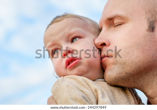 caring father calms toddler son outdoors on the sky background