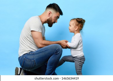 caring father and little obedient daughter who listens to the instruction of parent on blue isolated background. daddy making an observation to kid. dad asking daughter to behave well