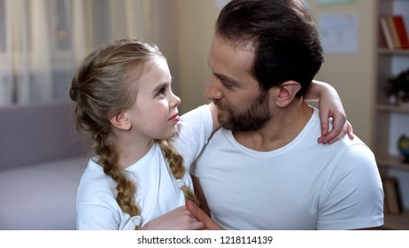 Caring father looking at cute daughter with love and hugging, happy parenthood