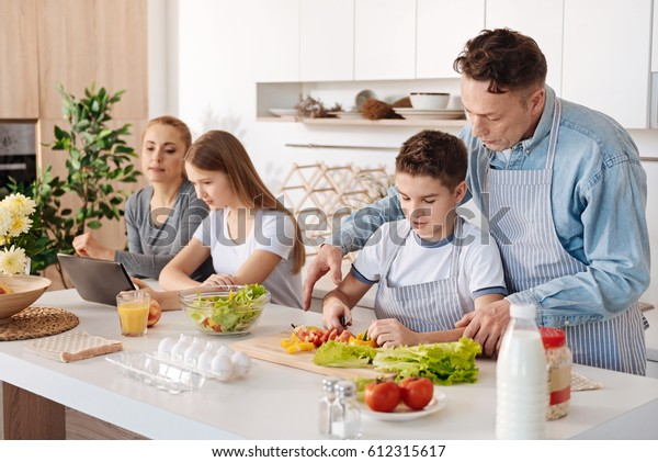Caring father teching his son to cook