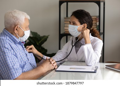 Caring female nurse in medical facemask listen to elderly patient heart with stethoscope in hospital. Woman GP or doctor in facial mask do checkup examine mature man client on consultation in clinic.