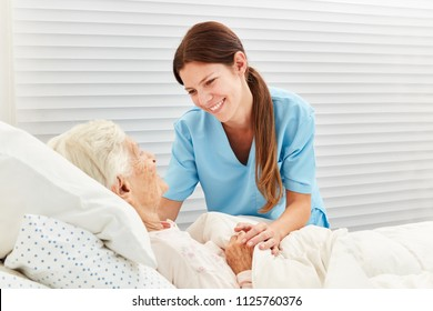 Caring geriatric nurse cares for ill senior citizen in nursing home or hospice