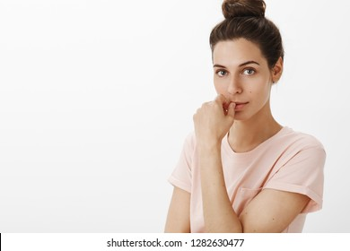 Caring good-looking flirty girlfriend with bun hairstyle in t-shirt standing half-turned looking sensual and intrigued as touching lip from desire and interest gazing at camera over gray wall