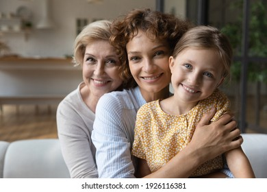 Caring grown woman mother hold on knees hug girl kid while mature female grandmother pensioner embrace her adult daughter from back. Family portrait of women dynasty look at camera sit on sofa cuddle