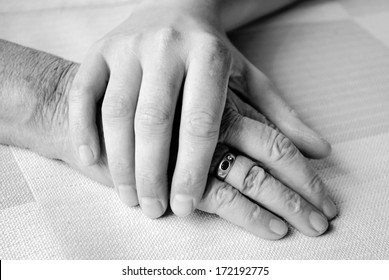 caring hand of a nurse and a senior patient