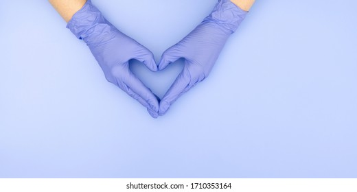 Caring hands of doctor in medical gloves making heart shape on blue background. Minimal medical concept. Flat lay, top view, copy space