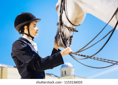 Caring horsewoman. Caring loving horsewoman wearing black jacket calming her white racing horse
