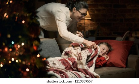 Caring loving mother tucking her child in, he is napping on the sofa on Christmas eve