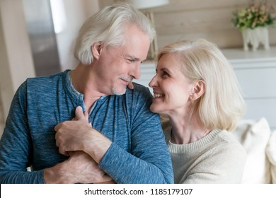 Caring loving senior old man admiring middle aged woman enjoying sincere feelings for many long years in happy marriage, romantic elderly mature smiling family couple looking at each other embracing