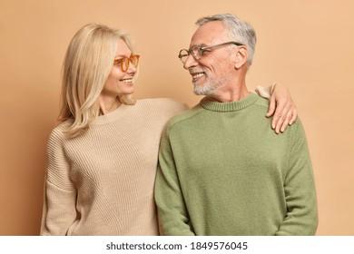 Die Sorge um die Frau mittleren Alters umarmt ihren Mann mit Liebe und einem breiten Lächeln. Verheiratetes reifes Paar hat gute Beziehungen einzeln auf braunem Hintergrund. Lächelnder Ehemann und Ehefrau für Foto