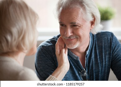 Caring middle aged woman gently stroking face of mature smiling handsome husband man looking at beloved wife, senior family enjoying love, understanding, warm feelings, older romantic couple dating