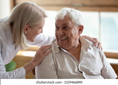 Caring middle-aged female licensed practical nurse in white coat talk to elderly patient 80s man, worker care about old healthcare consumer listens complaints give support, caregiving service concept