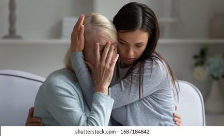 Caring millennial girl hug cuddle distressed upset mature mother crying suffering, loving grown-up adult daughter comfort caress depressed sad elderly mom, show support and understanding