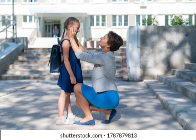 A caring mother get her daughter ready to school. A beautiful caucasian woman is squatting next to a little girl and sends her to study. Mother leads a little child school girl in first grade.