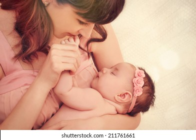 caring mother kissing little fingers of her cute sleeping baby girl, happy family concept
