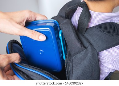 Caring mother puts blue plastic lunch box to her son in a school backpack.  School food or lunch, concept image. Selective focus, close-up.