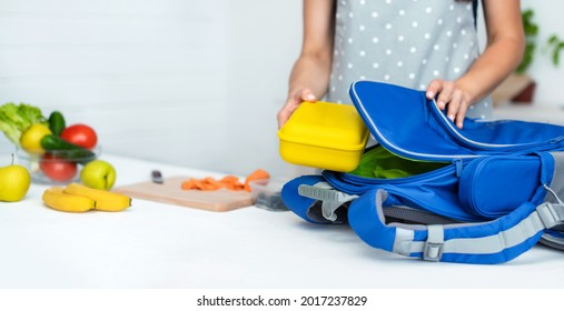 Caring mother puts yellow plastic lunch box to her son in a school backpack. School food or lunch, concept image. Selective focus, close-up.