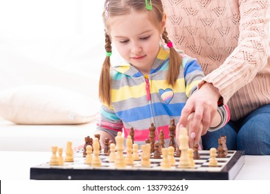 Caring mother teach pretty young lady to play chess herself