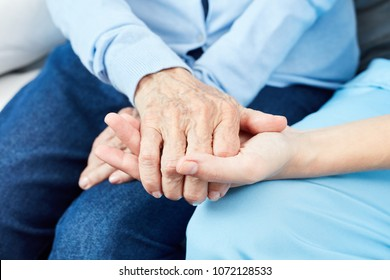 Caring nurse or geriatric nurse holds hand of an old woman