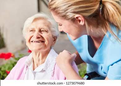 Caring Nurse Caring for Senior Woman in Wheelchair at Nursing Home