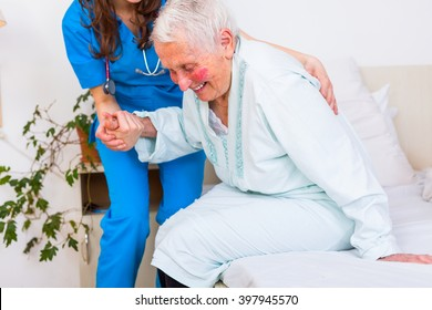 Caring nurse supporting her patient when she is getting up from bed after long time of illness.