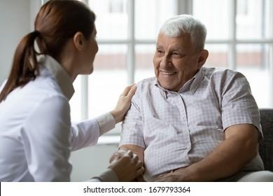 Caring nurse talks to old patient holds his hand sit in living room at homecare visit provide psychological support listen complains showing empathy encouraging. Geriatrics medicine caregiving concept