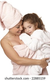 Caring nurturing mother cuddles her daughter at bathtime