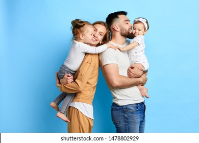 caring parents hugging their children, expressing love, warm feeling. close up photo. isolated blue background. studio shot