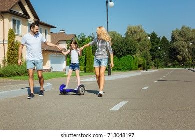Caring parents teaching daughter to ride hoverboard