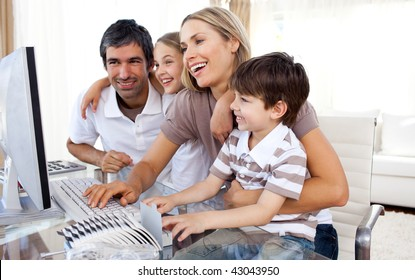 Caring parents teaching their children how to use a computer in the living-room