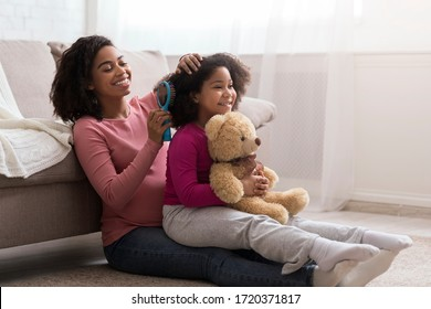 Caring pregnant african mom combing her little daughter's hair at home, sitting together on floor in living room, free space