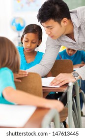 caring primary educator helping a student in classroom
