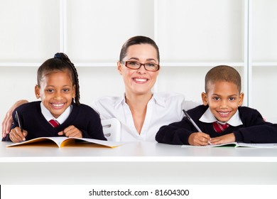caring primary teacher and students in classroom