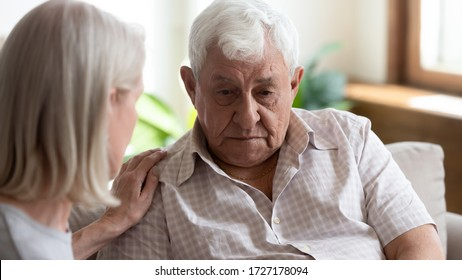 Caring senior woman touch support upset distressed elderly 80s husband mourning or yearning on couch in retirement house, loving mature wife comfort caress depressed old thoughtful unhappy husband