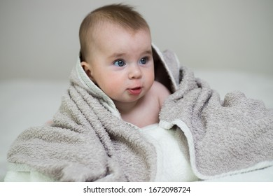 Caring for small child. Lovely baby with big blue eyes. 6 months. Lying on white blanket on his stomach looks to the right. Studio light. Beige towel on top. Head,face, hair are visible. Horizontal