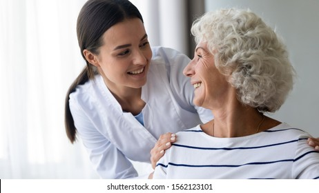 Caring smiling young nurse taking care supporting happy elder grandma patient, female doctor caregiver provide medical services helping old woman at homecare medical visit, seniors healthcare concept
