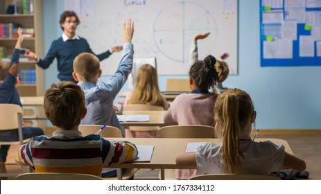 Caring Teacher Explains Lesson to a Classroom Full of Diverse Children. In School with Group of Smart Multiethnic Kids Learning Science, Whole Classroom Raising Hands Knowing Answer.