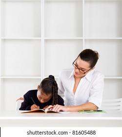 caring tutor helping schoolgirl with homework