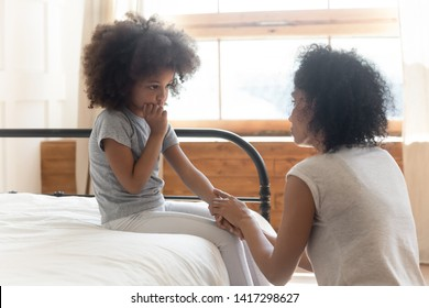 Caring worried african american mother holding hand of sad little mixed race daughter talking giving support and comfort, black mom foster parent consoling small kid being bullied sit on bed at home