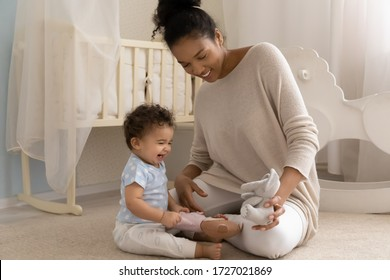 Caring young biracial mother sit on warm floor in children room playing with overjoyed small infant toddler, loving african American mom have fun entertain little ethnic baby child with funny toy