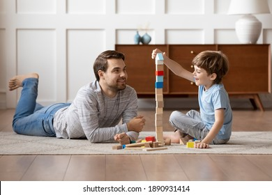 Caring young Caucasian father and small son sit on warm floor at home engaged in funny game together. Loving dad and little boy child have fun play build construct with wooden blocks bricks.