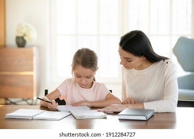 Caring young Caucasian mom and small 7s daughter sit at table at home handwriting make homework assignment together. Loving mother or nanny and little girl child study learn do home task.