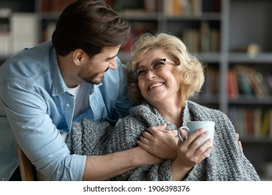 Caring young man covering happy middle aged old mother with plaid, giving cup of hot tea, showing love and devotion at home. Smiling retired woman enjoying peaceful comfort moment with grown son.