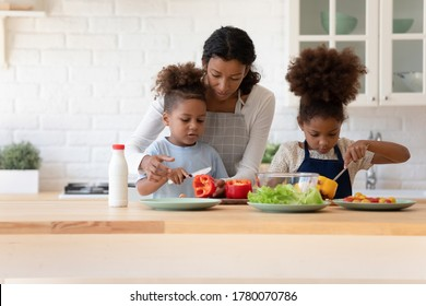 Caring young mom teach little ethnic children cook food at home kitchen, loving mother and small kids chop vegetables make healthy organic dinner salad together