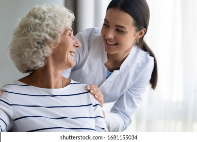 Caring young nurse support assist positive old lady patient at home or hospital, smiling female caregiver or doctor give help to optimistic mature senior grandmother, elderly healthcare concept