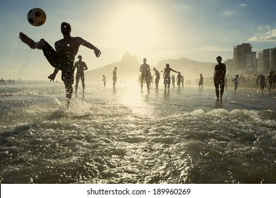 Carioca Brazilians playing altinho beach football in silhouettes kicking soccer balls in the waves of Ipanema Beach Rio de Janeiro Brazil